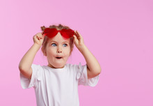 Portrait Of Surprised Cute Little Toddler Girl In The Heart Shape Sunglasses. Child With Open Mouth Having Fun Isolated Over Pink Background. Looking At Camera. Wow Funny Face