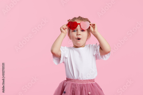 Obraz Portrait of surprised cute little toddler girl in the heart shape sunglasses. Child with open mouth having fun isolated over pink background. Looking at camera. Wow funny face - fototapety do salonu