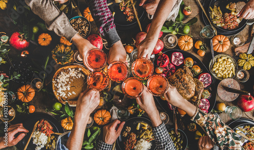 Poster Countryside Family celebrating Thanksgiving day. Flat-lay of feasting peoples hands clinking glasses with rose wine over Friendsgiving table with traditional Fall food, roasted turkey, pumpkin pie, top view