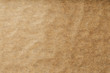 canvas print picture - A roll of unfolded brown parchment paper, for baking food in on a dark background, top view.