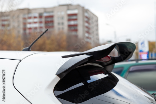 Photo  White car tuning rear spoiler view on the car parking in the street