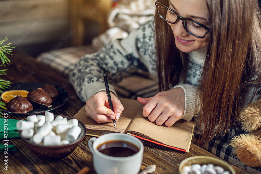 Fototapety, obrazy: Woman in a sweater is writing a wish list in a notebook in the warm atmosphere of Christmas. Cozy New Year mood