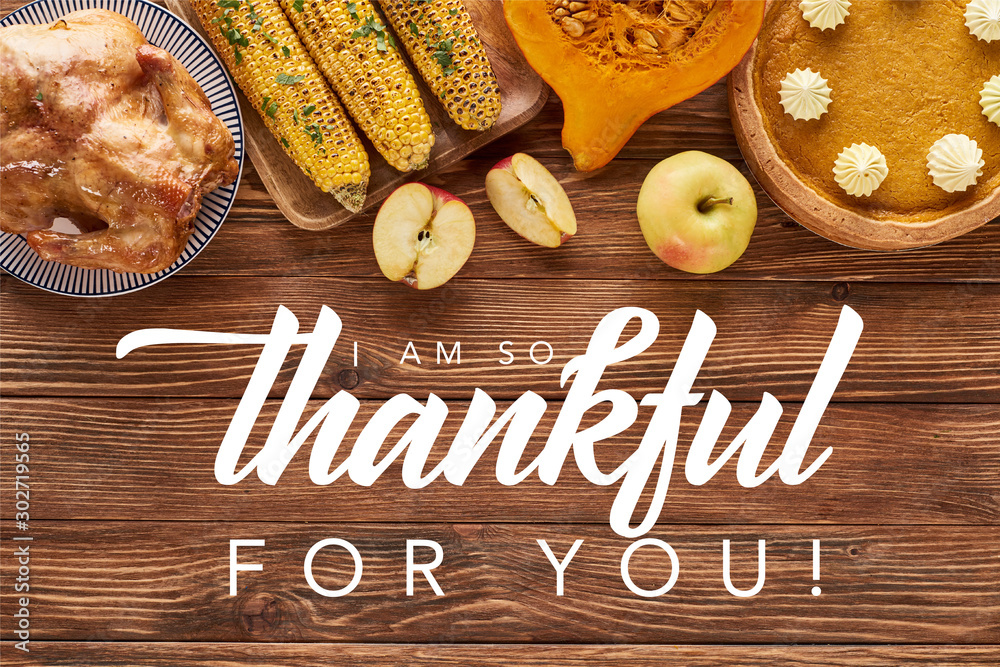 Fototapeta top view of pumpkin pie, turkey and vegetables served at wooden table with i am so thankful for you illustration