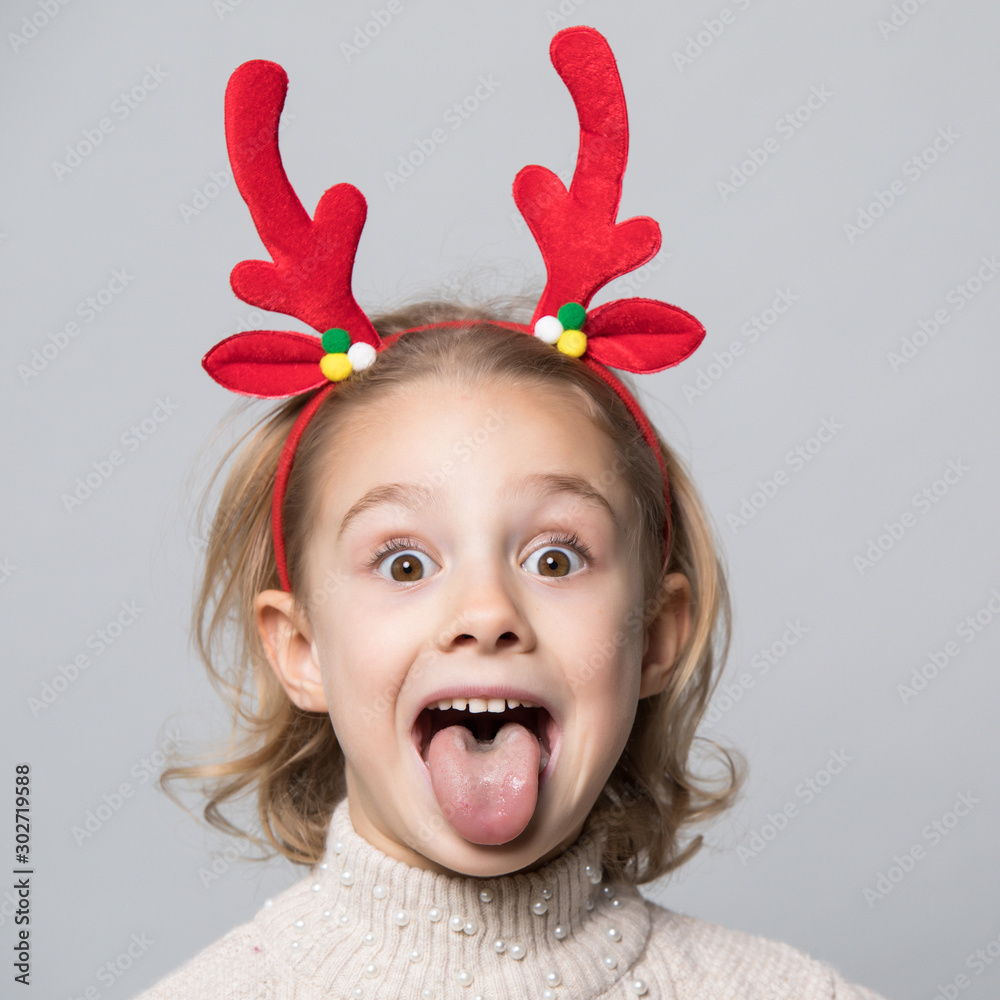 Fototapeta Cute young girl wearing deer horns. New year concept.