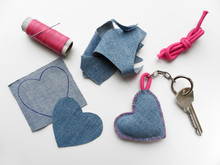 Desktop With Cut Cloth, Spool Of Thread With Needle, Pink Cord And Finished Keychain With Key. Handmade Gift. Valentine's Day Concept.