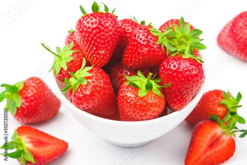Fotografía  Red ripe strawberry in the white bowl, light background