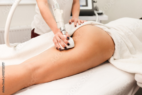 Doctor cosmetologist with a roller in his hands makes a buttocks massage with de Canvas Print