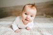 canvas print picture - Cute baby ginger hair close up crawling on bed smiling adorable kid portrait family lifestyle 3 month old child