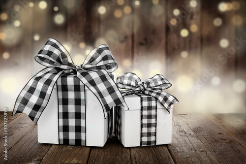 Fotobehang Europa Rustic Christmas gifts with black and white buffalo plaid check ribbon. Side view with a dark wood and twinkling light background.