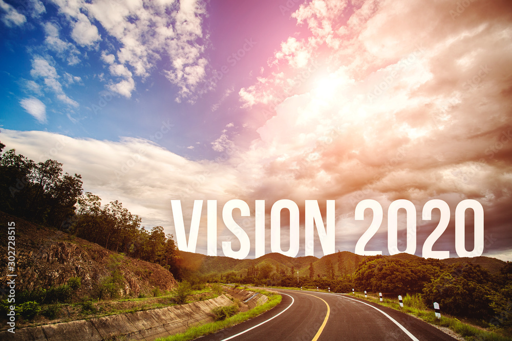 Fototapeta The word vision 2020 behind the tree of empty asphalt road at golden sunset and beautiful blue sky. Concept for vision year 2020.