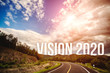 canvas print picture - The word vision 2020 behind the tree of empty asphalt road at golden sunset and beautiful blue sky. Concept for vision year 2020.