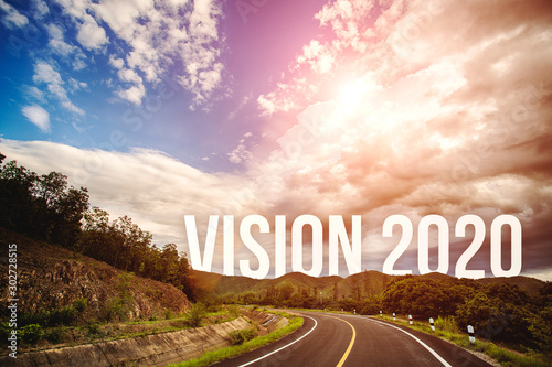 Fototapeta  The word vision 2020 behind the tree of empty asphalt road at golden sunset and beautiful blue sky