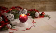 Christmas Setting: A Red Lit Candle With Cross Screen Effect On Foreground Surrounded By Pine Branches, Red Baubles, Red And White Ribbons, White Pine Cones On Christmas Tablecloth In Bokeh Effect