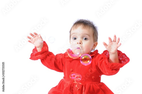 Photo Funny surprised little girl in red Christmas dresses plays with soap bubbles on white isolated background