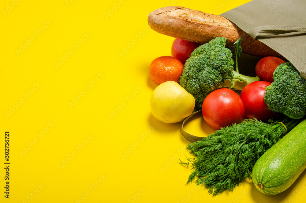 Fototapeta Food vegetable, bread, fruit in eco grocery bag on yellow background, top view