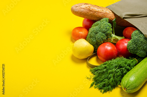 Obraz Food vegetable, bread, fruit in eco grocery bag on yellow background, top view - fototapety do salonu