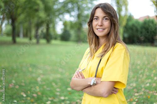 Photo Mujer enfermera joven y sonriente con uniforme amarillo y estetoscopio con los b