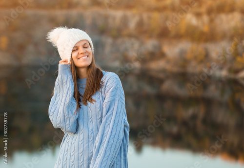 Winter portrait of smilling woman in white hat with big bubo makes funny face ou Canvas Print