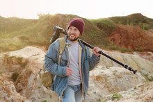 A Bearded Hipster Photographer Strolls Along The Shore Of A Sandy Quarry, With Equipment On His Shoulders And Looks Away With A Smile