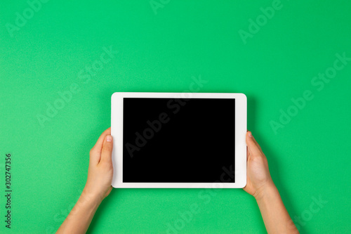Obraz Child hands holding tablet computer on light green background - fototapety do salonu