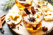 canvas print picture - Hot drink for New Year, Christmas or autumn holidays. Mulled cider or spiced tea or mulled white wine with lemon, apples, cinnamon, anise, cloves.