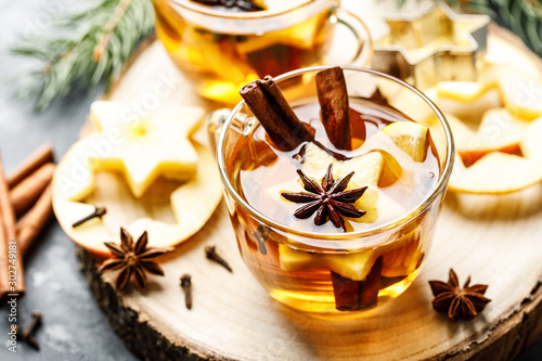 Foto auf Leinwand Tee Hot drink for New Year, Christmas or autumn holidays. Mulled cider or spiced tea or mulled white wine with lemon, apples, cinnamon, anise, cloves.
