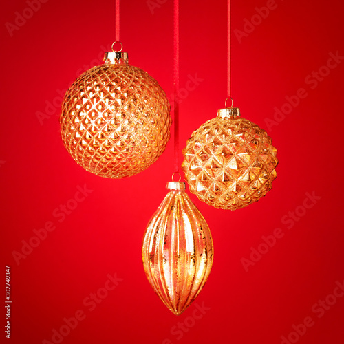 Fototapeta Three golden Christmas baubles hanging against the red background. New Year greeting card. Selective focus. obraz na płótnie