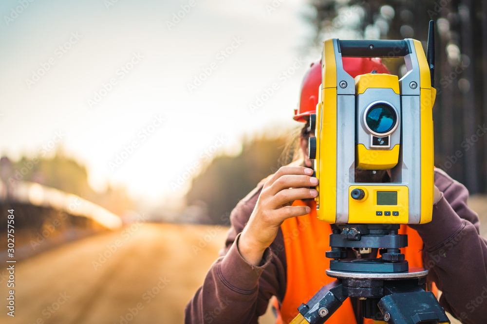 Fototapety, obrazy: Surveyor engineer with equipment (theodolite or total positioning station) on the construction site of the road or building with construction machinery background
