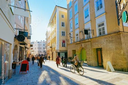 Fototapeta premium Kobieta na rowerze na ulicy starego miasta Salzburga w Austrii. Turyści i ludzie w mieście Mozart, Europa, zima. Panorama i punkt orientacyjny. Pejzaż miejski z rozbłyskiem słońca. Sklepy i sklep. Architektura budynku