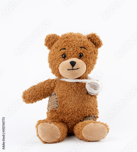 brown teddy bear with rewound white bandage paw on a white background #302765773