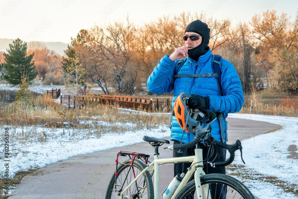 Fototapeta putting balaclava and helmet on for winter biking