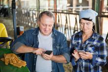 Senior Man And Female Farmers Using Phones On Farm