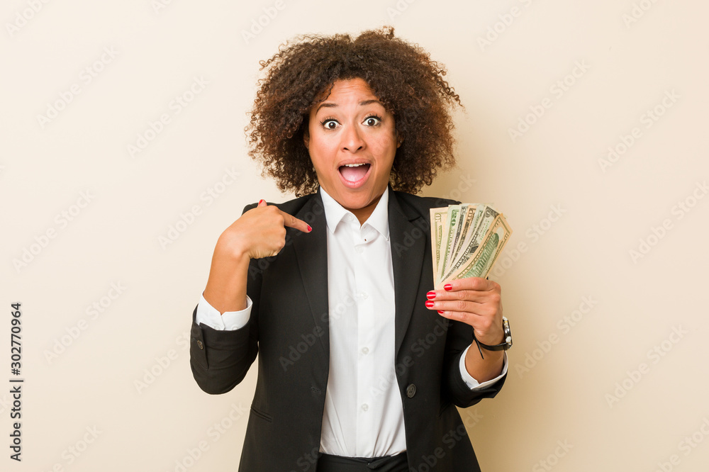 Fototapety, obrazy: Young african american woman holding dollars surprised pointing at himself, smiling broadly.