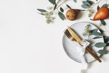Autumn Thanksgiving Table Place Setting. Golden Cutlery, Porcelain Plate, Berry Eucalyptus Leaves And Branches, Silk Ribbon And Pear Fruit On White Table Background. Fall Wedding. Flat Lay, Top View.