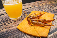 Dried Mullet On A Wooden Board With A Mug Of Beer On The Table. Fish And Seafood Cuisine. Tasty Snack.