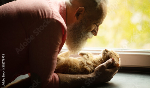 Leinwand Poster  Senior man holding cute red cat at home. Man and cat hugging.