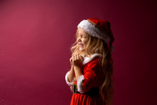 Little Blonde Girl In A Santa Costume Holds Her Hands To Her Face And Makes A Wish.red Background. Space For Text. Dreams Come True. Merry Christmas!