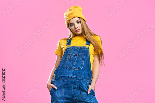 Portret a pretty girl in denim overalls and a yellow hat on a pink background Fototapeta