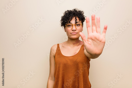 Fotografía  Young african american woman with skin birth mark standing with outstretched hand showing stop sign, preventing you