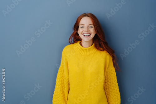 Joyful young redhead woman laughing at camera
