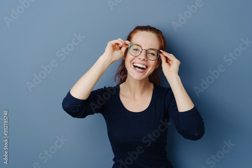Fototapeta Cute laughing young woman wearing spectacles
