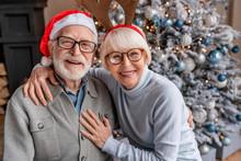 Portrait Of Happy Smiling Senior Couple In Santa Hats Celebrating At Home