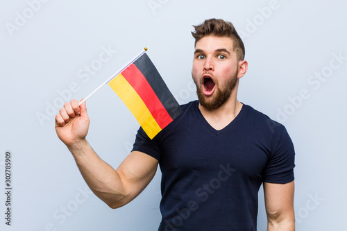 Fotografija  Young caucasian man holding a germany flag impressed holding copy space on palm