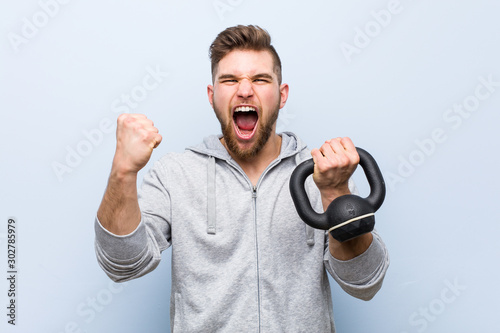 Obraz Young caucasian sportsman holding a dumbbell cheering carefree and excited. Victory concept. - fototapety do salonu