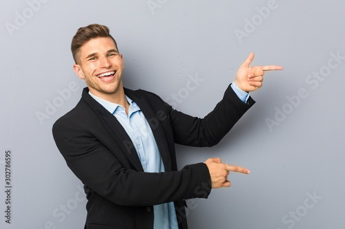 Young handsome caucasian man excited pointing with forefingers away Fototapete