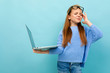 Leinwanddruck Bild - half-length shot of a schoolgirl on a blue background with tired eyes, glasses on her forehead in the hands of a laptop
