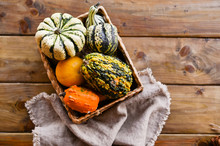 Different Thanksgiving Mini Pumpkins On A Rustic Wooden Table. Thanksgiving Concept. Autumn, Harvest Wicker Basket