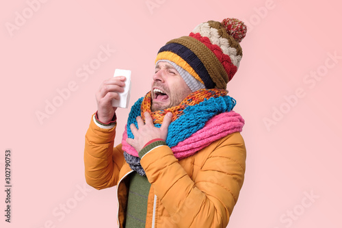 Valokuva  Young funny man in several hats ans scarfs man with handkerchief sneezing being ill