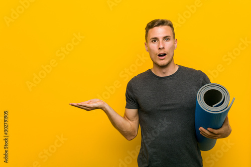 Young caucasian man holding a mat impressed holding copy space on palm Fototapeta