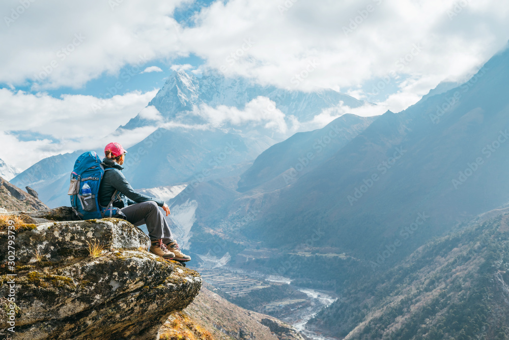 Fototapety, obrazy: Young hiker backpacker female sitting on the cliff edge and enjoying Ama Dablam 6,812m peak view during Everest Base Camp (EBC) trekking route near Phortse, Nepal. Active vacations concept image